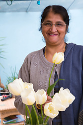 Older woman at home arranging some flowers,