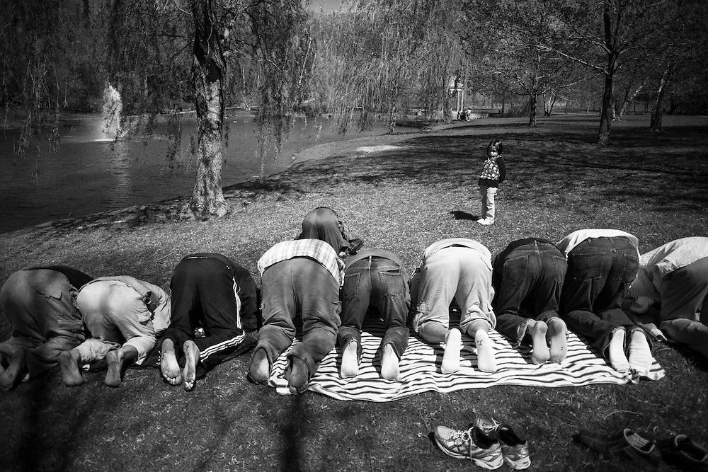 A girl looks at Men praying at a park.