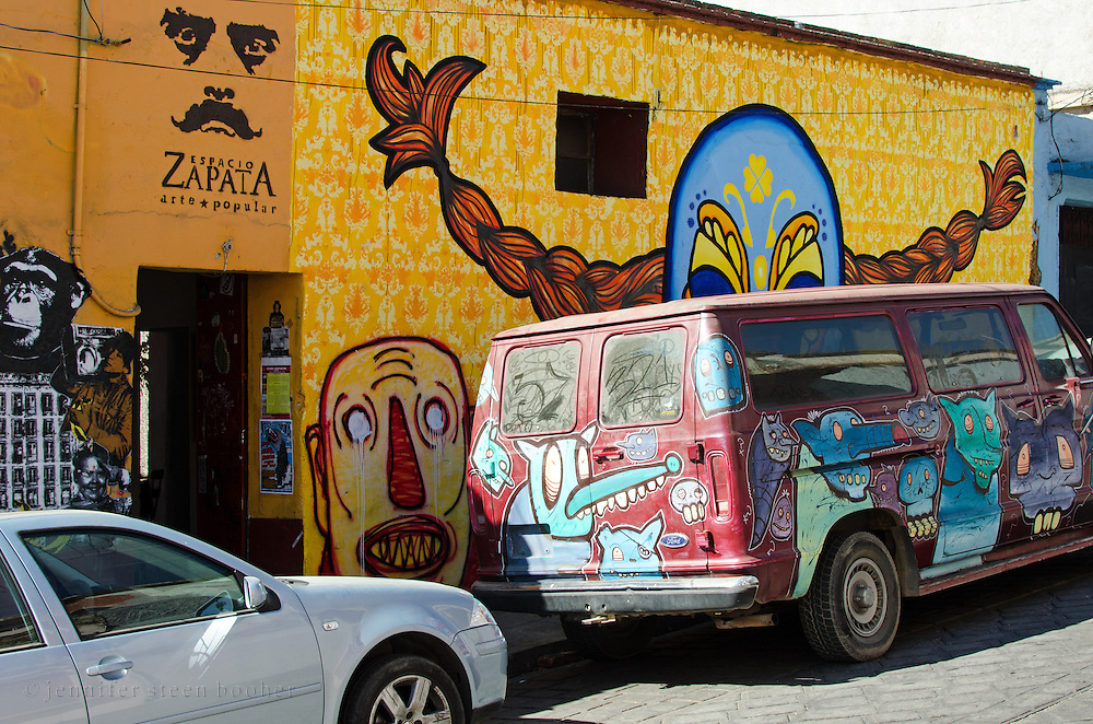 """Outside the Espacio Zapata gallery in Oaxaca, a mural of """"Luchadora Longstocking"""" by the Kollektivet Livet looms over a van covered with monsters painted by the graffiti artist 'SCOM' (Society Creates all the Monsters.)"""