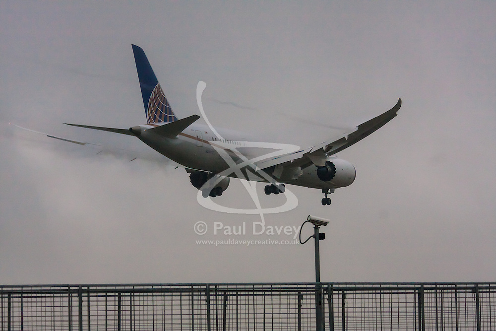 """January 3rd 2015, Heathrow Airport, London. Low cloud and rain provide ideal conditions to observe wake vortexes and """"fluffing"""" as moisture condenses over the wings of landing aircraft. With the runway visible only at the last minute, several planes had to perform a """"go-round"""", abandoning their first attempts to land. PICTURED: Wake vortices stream from the flaps of a Continental Boeing 787 Dreamliner moments before it lands on Heathrow's runway 27L."""