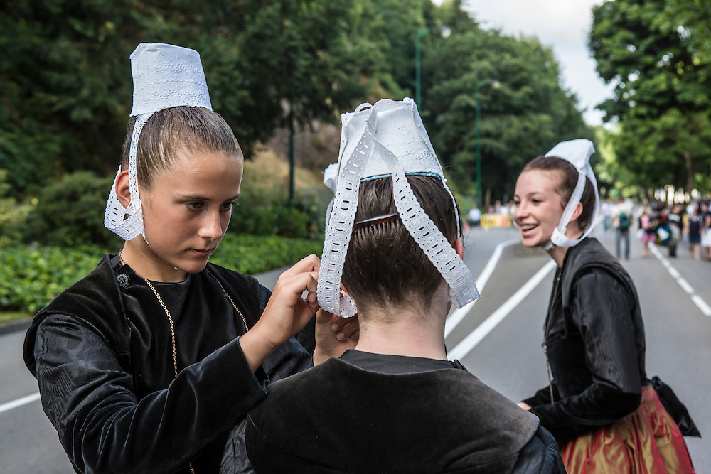 Girls from nearby Pluguffan put the final touches on their outfits before the Great Parade at the Festival de Cornouaille on Sunday, July 24, 2016 in Quimper, France.
