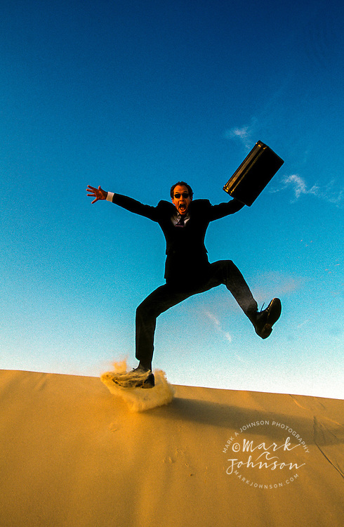 Australia, Qld., businessman leaping off sand dune