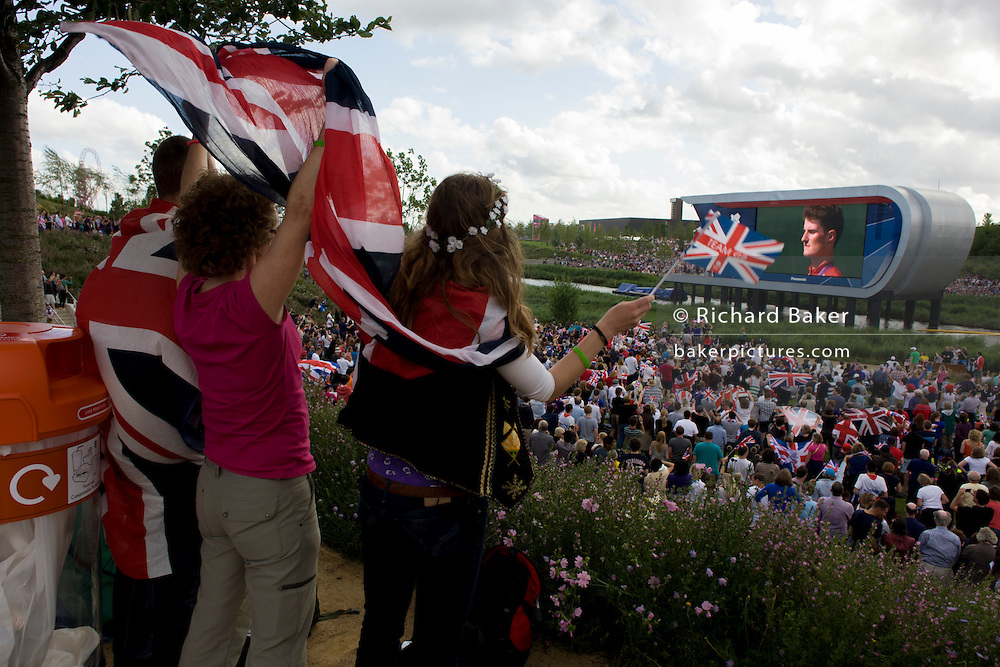 Families and spectators sing the British national anthem during a medal ceremony for shooting gold medallist Peter Robinson in the Olympic Park during the London 2012 Olympics. The planting of 4,000 trees, 300,000 wetland plants and more than 150,000 perennial plants plus  nectar-rich wildflower make for a colourful setting for the Games. This land was transformed to become a 2.5 Sq Km sporting complex, once industrial businesses and now the venue of eight venues including the main arena, Aquatics Centre and Velodrome plus the athletes' Olympic Village. After the Olympics, the park is to be known as Queen Elizabeth Olympic Park.