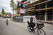 In Zeist fietst een moeder met haar kinderen langs een nieuwbouwproject in het centrum.<br /> <br /> In Zeist a woman cycles with her children at the city center.