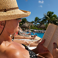 A woman reads a book while sunbathing by a resort pool.