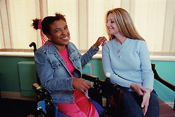 Care manager and young woman with Cerebral Palsy laughing together in residential care centre,