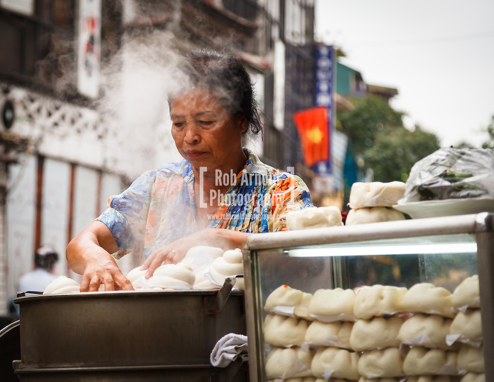 19/04/2013 - Hanoi, Vietnam. A Vietnamese woman in the Old Quarter of Hanoi selling Banh Bao (steamed dumplings). Photo by Rob Arnold