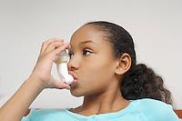 Girl (7-9) using inhaler in hospital
