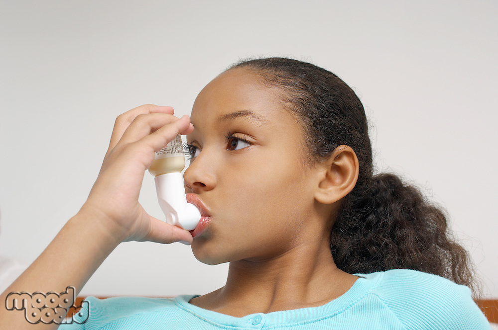 Girl (7-9) using inhaler in hospital