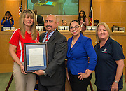 Connie Watt, left, accepts a resolution from Michael Cardona and Ruth Ruiz during a meeting of the Houston ISD Board of Trustees, March 10, 2016.