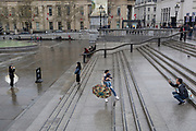 Tourists take photos on the steps outside the National Gallery in Trafalgar Square, Westminster, on 9th April 2019, in London, England.