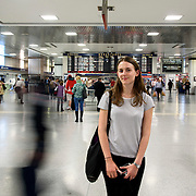 May 24, 2016 - New York, NY :  Hannah Greenberg, in black pants and striped top, waits for her train to New Jersey in the Amtrak Concourse on Penn Station's upper level during the evening rush on Tuesday. Above her, music filters into the space through a series of in-ceiling speakers (not visible). CREDIT: Karsten Moran for The New York Times