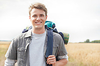 Portrait of handsome male hiker with backpack standing on field