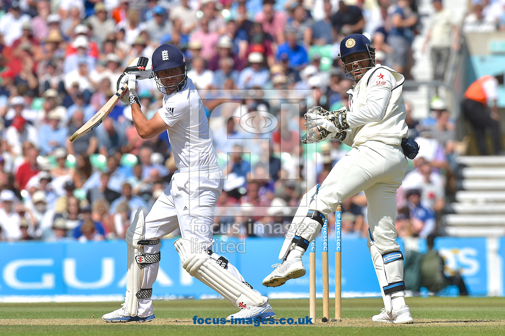 Captain Alastair Cook of England looks back with Captain and wicketkeeper Mahendra Singh Dhoni of India  to see his edged shot dropped by the slip (out of shot) during the Investec Test Match match at the Kia Oval, London<br /> Picture by Alan Stanford/Focus Images Ltd +44 7915 056117<br /> 16/08/2014