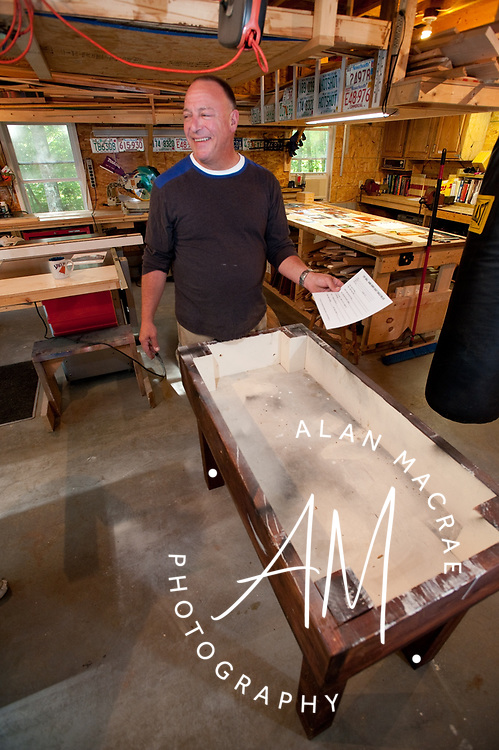 "Alan Korb holds his trademark registration document as he stands behind the base of his original ""Tuff Table"" play table in his Belmont workshop.  (Alan MacRae/for the Citizen)"
