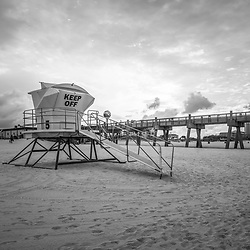 Pensacola Beach lifeguard tower five and Gulf Pier sunrise black and white photo on Casino Beach. Pensacola Beach Florida is a coastal city on Santa Rosa Island in the Emerald Coast of the Southeastern United States of America. Copyright ⓒ 2018 Paul Velgos with All Rights Reserved.