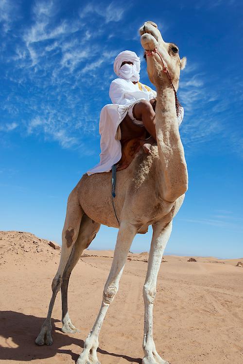 Nomad on dromedary in the Sahara desert against cloudy blue sky.