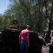 Locals check a military tank, set alight hours after deadly clashes between separatists armed groups and the Ukrainian Army over the control of key buildings in the city.