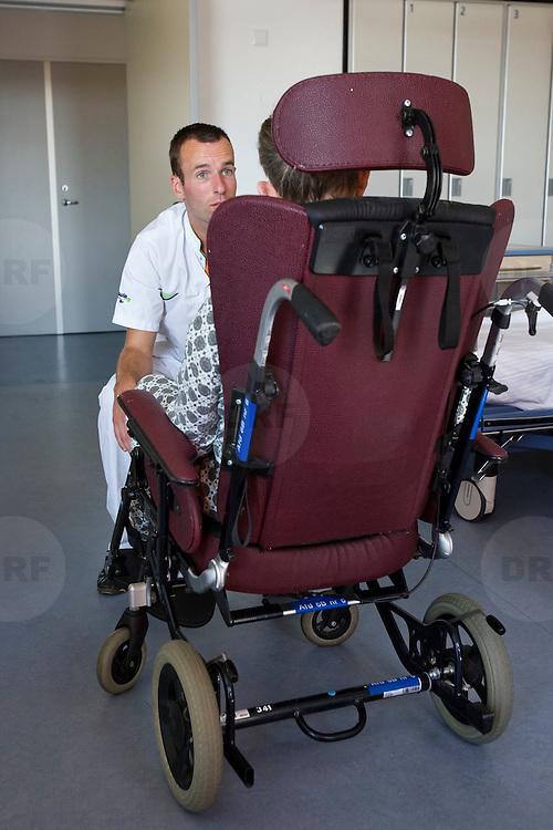 Nederland Rotterdam  31-08-2009 20090831 Foto: David Rozing .Serie over zorgsector, Ikazia Ziekenhuis Rotterdam. Afdeling neurologie, stroke unit, revalidatie  bejaarde man op zaal. Broeder praat met patient,     na de  oefeningen om opnieuw te leren lopen. De patient heeft een beroerte gehad en daardoor is oa zijn ( grove ) motoriek aangetast, deels verlamd geraakt. rolstoel, wheelchair.  Revalidation old patient, nurse talks to patient who has suffered a stroke. Na een ernstige beroerte wordt u opgenomen in een gespecialiseerde afdeling of een afdeling intensieve zorgen van het ziekenhuis. Na de eerste 24 uur is het nodig om een aangepast revalidatieprogramma te starten. dat kan bestaan in wisselhoudingen en passieve bewegingen van de verlamde lichaamshelft.  .  ..Foto: David Rozing ..Holland, The Netherlands, dutch, Pays Bas, Europe, ronde doen, routine verpleegkundigen , verpleger, verplegers, verplegend, status.,interactie patient verpleging, tijd hebben voor, aandacht hebben voor geven,  hulp, helpen,, nursing, aansterken, handeling, handelingen,Holland, The Netherlands, dutch, Pays Bas, Europe, menselijk contact ,   oud, oude, op leeftijd, revalidatie, revalideren, revalidation, nursing,steun, steunen, warmte geven, helpen, hart onder de riem steken,aanmoedigen,onherkenbaar, onherkenbare, unrecognisable,copy space, ruimte voor tekst,  , mobiliteit, niet mobiel zijn, verlamd zijn, niet goed kunnen lopen, ,zorgverlener, zorgverleners,zorgverlening,ondersteunen, helpen te met,moral support, blijk van affectie, steuntje in de rug,  steunbetuiging, verpleger, verplegers, verplegend