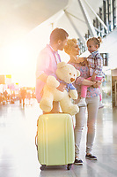 Happy family on a holiday arriving at the airport with lens flare