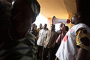 A Benin Red Cross volunteer gives directions to flood victims during a UNICEF-sponsored distribution session in Athieme, Benin  on Monday October 25, 2010. UNICEF donated water treatment tablets, mosquito nets and soap to affected families, while other partner organizations offered blankets, floormats, and buckets.