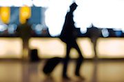 Out of focus, anonymous passengers pass-by against strong backlight in Departures at Heathrow Airport's Terminal 5.