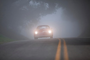 Image of a red 1958 Porsche Carrera GT Speedster driving on a country road in fog, Santa Barbara, California, America west coast