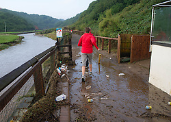 © Licensed to London News Pictures. 07/09/2013<br /> <br /> Saltburn, Cleveland, England<br /> <br /> Two runners make their way through mud and rubbish alongside a river bank following an evening of torrential rainfall that caused flooding and disruption to Saltburn in Cleveland.<br /> <br /> Photo credit : Ian Forsyth/LNP