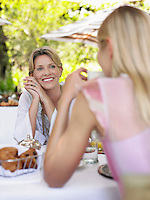 Two women sitting at table having conversation selective focus
