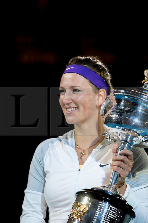 © Licensed to London News Pictures. 26/01/2013. Melbourne Park, Australia. Victoria Azarenka holds up her winners trophy while smiling  during the Womens Final between Victoria Azarenka and Li Na of the Australian Open. Photo credit : Asanka Brendon Ratnayake/LNP
