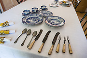 Antique table setting: spoons, knives, two-tine forks, plates & cups. Conner Prairie Interactive History Park provides family-friendly fun for all ages in Fishers, Indiana, USA. Founded by pharmaceutical executive Eli Lilly in the 1930s, Conner Prairie living history museum now recreates life in Indiana in the 1800s on the White River and preserves the William Conner home (listed on the National Register of Historic Places).