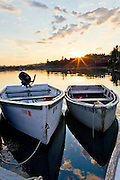 Boats sit next to a dock at sunrise Addison, Maine.