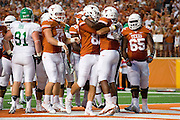 AUSTIN, TX - AUGUST 30:  Malcolm Brown #28 of the Texas Longhorns celebrates with teammates after scoring a touchdown against the North Texas Mean Green on August 30, 2014 at Darrell K Royal-Texas Memorial Stadium in Austin, Texas.  (Photo by Cooper Neill/Getty Images) *** Local Caption *** Malcolm Brown
