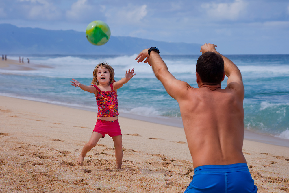A little girl excitedly reaches to catch a ball on the beach in Hawaii