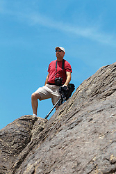 Adult male photographer standing on rock formation, Death Valley National Park, California, United States of America