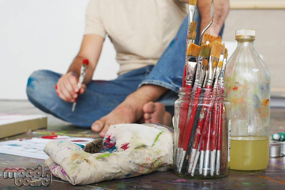 Artist sitting on floor focus on paint brushes and materials