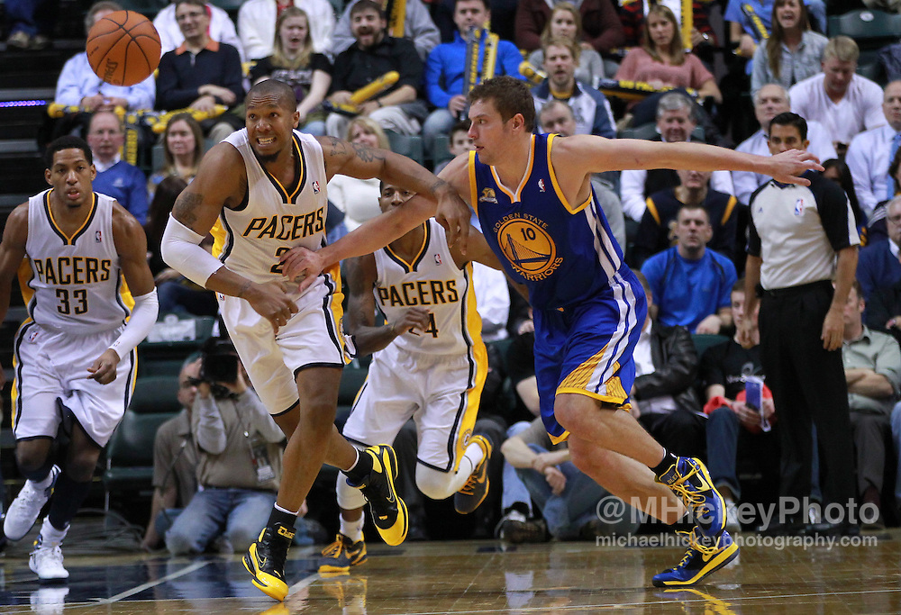 Feb. 28, 2012; Indianapolis, IN, USA; Indiana Pacers power forward David West (21) and Golden State Warriors power forward David Lee (10) scramble for a loose ball at Bankers Life Fieldhouse. Indiana defeated Golden State 102-78. Mandatory credit: Michael Hickey-US PRESSWIRE