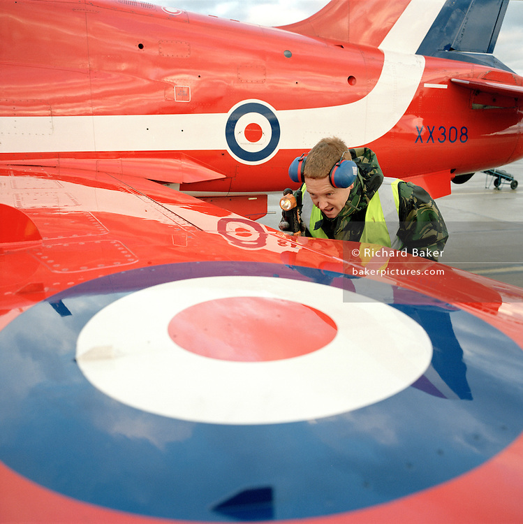 Junior Technician Brian Robb, an engineer with the elite 'Red Arrows', Britain's prestigious Royal Air Force aerobatic team, shines his torch inside the flaps of a Hawk jet aircraft checking for obstructions, RAF Scampton, Lincolnshire. Wearing ear defenders clasped to his head, J/Tech Robb peers into the wing assembly during a pre-flight inspection before the pilot emerges from for another winter training flight. Robb is a member of the team's support ground crew who outnumber the pilots 8:1 and without them, the Red Arrows couldn't fly.  Eleven trades are imported from some sixty that the RAF employs and teaches. Crouching by an RAF roundel emblem, he wears an army style green camouflage coat as protection over the biting Lincolnshire wind, and a fluorescent tabard required for any personnel working on the 'line', where the aircraft taxi to and park. .