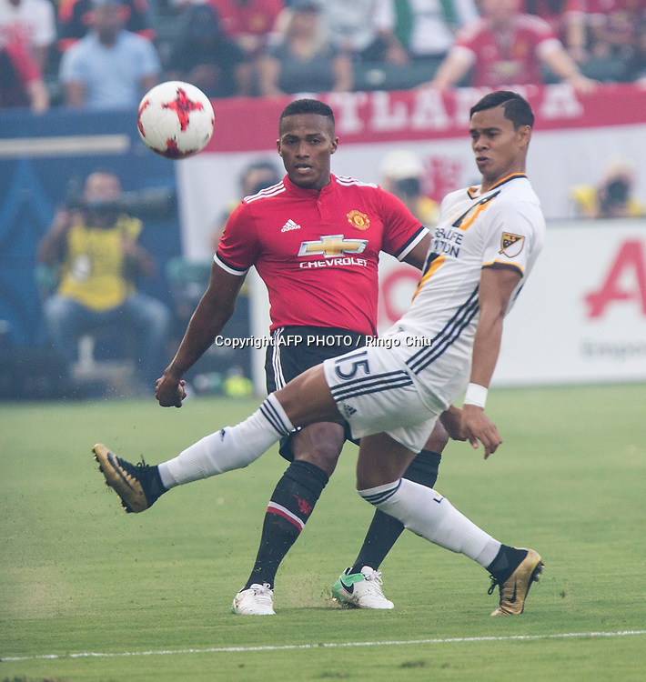 Manchester United Antonio Valencia, left, and Los Angeles Galaxy Ariel Lassiter battle for the ball during the first half of a national friendly soccer game at StubHub Center on July 15, 2017 in Carson, California.   AFP PHOTO / Ringo Chiu