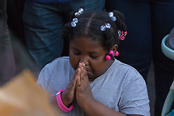 London, June 15th 2017. Local residents and well-wishers gather at a short vigil outside Notting Hill Methodist Church near the scene of the Grenfell Tower Fire Disaster in which so far seventeen people have been reported killed, with dozens injured, many still missing and scores of people rendered homeless. PICTURED: A Girl prays as a minute's silence is observed.
