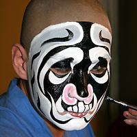 Asia, China, Beijing. Opera performer applies make up mask.