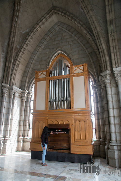 Visitor examines an organ in the Basilica del Voto Nacional in Quito, Ecuador.