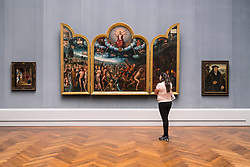 Woman looking at Jean Bellengambe's, Triptychon mit dem Jungsten Gericht at Gemaldegalerie museum, at Kulturforum in Berlin, Germany