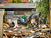 16 NOVEMBER 2015 - BANGKOK, THAILAND:   A small excavator is being used to tear down homes in the Wat Kalayanamit neighborhood. Fifty-four homes around Wat Kalayanamit, a historic Buddhist temple on the Chao Phraya River in the Thonburi section of Bangkok, are being razed and the residents evicted to make way for new development at the temple. The abbot of the temple said he was evicting the residents, who have lived on the temple grounds for generations, because their homes are unsafe and because he wants to improve the temple grounds. The evictions are a part of a Bangkok trend, especially along the Chao Phraya River and BTS light rail lines. Low income people are being evicted from their long time homes to make way for urban renewal.          PHOTO BY JACK KURTZ