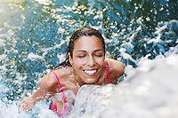 Young woman standing under waterfall high angle view