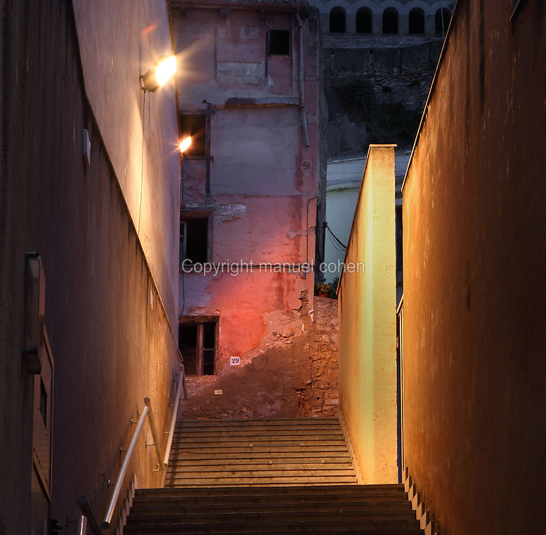 Narrow streets and steps at night in the old town or Casc Antic of Tortosa, Tarragona, Spain. Tortosa is an ancient town situated on the Ebro Delta which has a rich heritage dating from Roman times. In recent years, many buildings in the old town have been abandoned and fallen into disrepair. Picture by Manuel Cohen