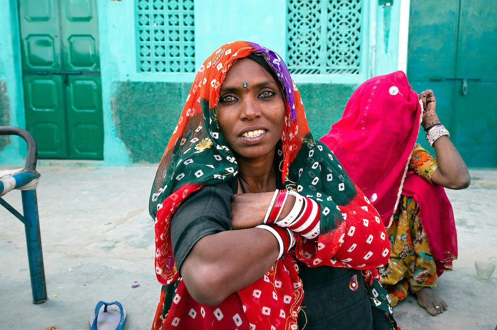 Very colourful, traditionally dresed woman from the Bhopa community, sits in front of her mother in front of their house in Rajasthan (India)