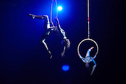 Circus acrobats perform high above auditor staff during a company Academy Day held for 3,000 of their London employees at Excel in London's Docklands England. Lit with blue light by powerful spotlights, the two girls are suspended in mid-air using hoops attached to safety ropes. They both make dramatic shapes in the air to demonstrate confidence, synchronised teamwork and co-operation between partners, the themes of this corporate day out of the office. The employees out of sight below are attending this fair where motivational pep-talks from executives, outside speakers and gurus will talk to large groups of personnel so their presence on this day away from the office is vital for the year's business ahead.