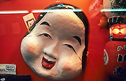"""Closeup view of large mask known as """"Otafuku"""" hangs in the window display of a souvenir shop in Kawagoe, Saitama Prefecture, Japan..The otafuku represents happiness and good fortune, and the masks are used in traditional Japanese theatre and dance."""