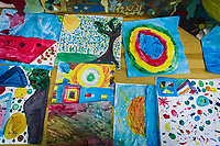 """NAPLES, ITALY - 16 MARCH 2018: Abstract paintings made by children during their after-school activity are seen here at """"Il Tappeto di Iqbal"""" (Iqbal's carpet), a non-profit cooperative in Barra, the estern district of Naples, Italy, on March 16th 2018.<br /> <br /> Il Tappeto di Iqbal (Iqbal's Carpet) is a non-profit cooperative founded in 2015 and Save The Children partner since 2015 that operates in the Naple's eastern neighborhood of Barra children in the arts of circus, theater and parkour. It was named after Iqbal Masih, a Pakistani boy who escaped from life as a child slave and became an activist against bonded labor in the 1990s.<br /> Barra, which is home to some 45,000 people, has the highest rate of school dropouts in the Italian region of Campania. Once a thriving industrial community, many of the factories were destroyed in a 1980 earthquake and never rebuilt. The resulting de-industrialization turned Barra into a poor, decaying neighborhood. There are no cinemas, theaters, parks or public spaces in Barra.<br /> The vast majority of children from poor families are faced with the choice of working in the black economy or joining the ranks of the organised crime.<br /> Recently, Save the Children Italy opened a number of educational and social spaces in Barra. The centers, known as Punti Luce, or points of light, aim to help local kids stay out of the ranks of the organised crime and have also become hubs for Iqbal's Carpet to work."""